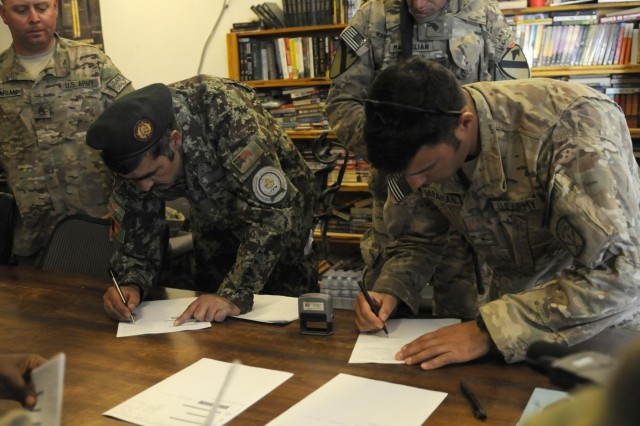 Afghan Maj. Raheem Shama (left), commander of the Afghan National Army Ammunition Depot (22 Bunkers), along U.S. Army Warrant Officer Alexander Arabian the ammunition accountable officer with the 63rd Ordnance Company, 101st Special Troops Battalion, 101st Sustainment Brigade (Task Force Lifeliner) sign ammunition transfer documents at Bagram Air Field, Parwan province, Afghanistan on Aug. 26, 2013. The transfer of ammunition from Coalition partners to the ANA is in response to a shortage of small arms ammunition in the Southern regions of Afghanistan. www.facebook.com/lifeliner (U.S. Army photo by Sgt. Sinthia Rosario, Task Force Lifeliner Public Affairs)