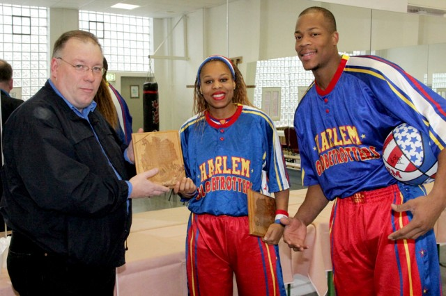 Kevin Griess, left, USAG Ansbach deputy commander, presents Sweet-J, middle, and Hacksaw, right, of the Harlem Globetrotters commemorative plaques Dec. 8, 2013, at Bunch Fitness Center.