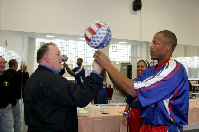 Kevin Griess, USAG Ansbach deputy commander, gets to show his skills to Hacksaw, right foreground, and Sweet-J, right background, before the Harlem Globetrotter performance Dec. 8 at Bunch Fitness Center.