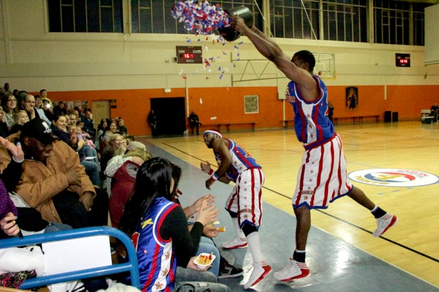 Hi-Lite fools the crowd in believing he had water in his bucket and dumps confetti on them during the Harlem Globetrotter performance Dec. 6, 2013, at Bunch Fitness Center at USAG Ansbach's Storck Barracks.