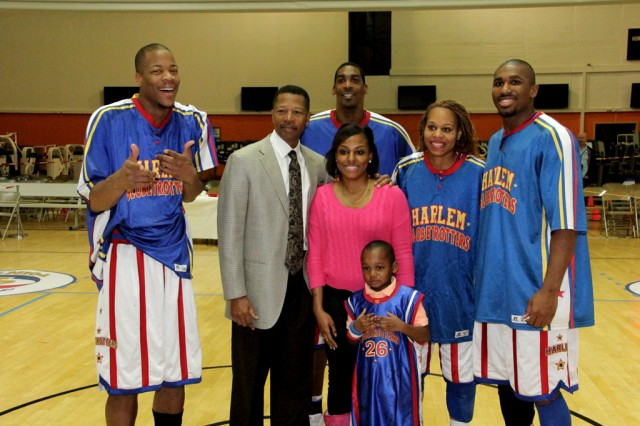 A lucky family gets a photo with Hacksaw, coach Jimmy Blacklock (a previous Harlem Globetrotter himself), Hi-Lite, Sweet-J and Thunder after the Harlem Globetrotter performance Dec. 6, 2013, at Bunch Fitness Center at USAG Ansbach's Storck Barracks.