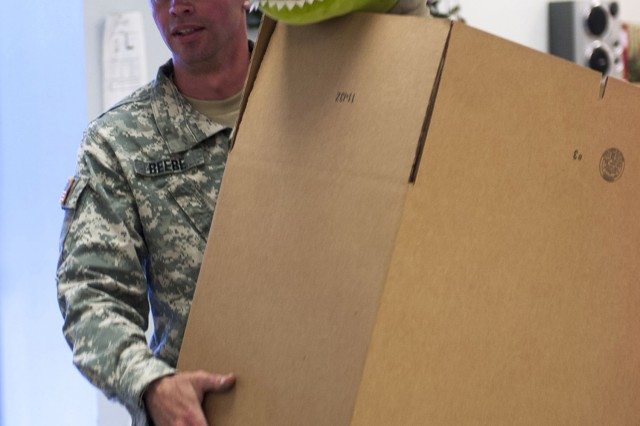 Spc. Kyle Beebe, a wheeled vehicle mechanic assigned to Headquarters and Headquarters Company, 13th Sustainment Command (Expeditionary), helps unload boxes of donated toys to the Santa's Workshop at Fort Hood, Texas, Dec. 3.  Santa's Workshop collects donations of toys, books and games to give to Fort Hood's active duty military Families who need additional assistance buying gifts during the holiday season. (Photo by Sgt. Angel Turner, 1st Cav. Div. PAO)