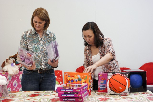 Lisa Rogers (left), a toy buyer, and Lisa West (right), president of Santa's Workshop, sort through donated toys on Fort Hood, Texas, Dec. 3. Central Texas businesses donate toys and other gifts for Fort Hood's active duty Soldiers, who need financial assistance during the holiday season. West, who is a volunteer with Santa's Workshop, describes her job as a labor of love and said Santa's Workshop is the most rewarding volunteer work that she has done as an Army volunteer. (Photo by Sgt. Angel Turner, 1st Cav. Div. PAO (Released)