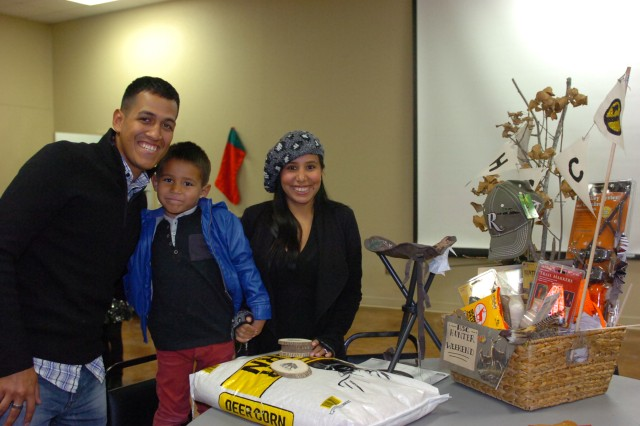 Spc. Aaron Morante, an armorer assigned to Headquarters Support Company, Headquarters and Headquarters Battalion, 1st Cavalry Division, his wife SanJuana and son Tristan, claim their gift basket during a holiday party Cove Civic Center, Dec. 5. The Morante Family won the basket following a raffle drawing. (Photo by Sgt. Angel Turner, 1st Cav. Div. PAO (Released)