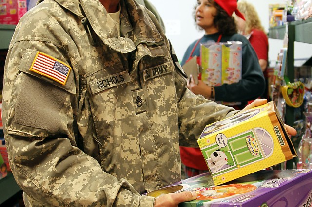 "Staff Sgt. Jeremiah Nichols, a San Jose, Calif., native and a motor transport operator assigned to Battery F of the 1st ""Dragon"" Battalion, 82nd Field Artillery Regiment, 1st ""Ironhorse"" Brigade Combat Team, 1st Cavalry Division, compares toys while choosing a gift for his daughter at Santa's Workshop, Dec. 5, at Fort Hood, Texas. Santa's Workshop is a non-profit, volunteer-run organization providing toys to Fort Hood's active-duty Families in need of a little extra help during the holidays. (U.S. Army photo by Pfc. Paige Pendleton, 1st BCT, 1st Cav. Div. PAO)"