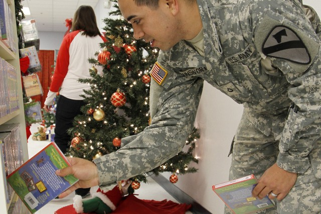 "Pfc. Josh Ainsworth, a San Antonio native and cannon crewmember assigned to Battery A of the 1st ""Dragon"" Battalion, 82nd Field Artillery Regiment, 1st ""Ironhorse"" Brigade Combat Team, 1st Cavalry Division, selects Family movies for his son at Santa's Workshop, Dec. 5, at Fort Hood, Texas. Santa's Workshop stocks everything from games and Family movies to bikes and fishing poles. (U.S. Army photo by Pfc. Paige Pendleton, 1st BCT, 1st Cav. Div. PAO)"