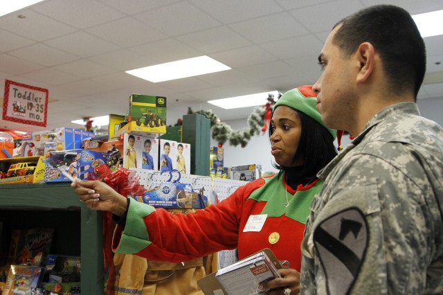 "Maj. Sylvia Johnson (left), a Luverne, Ala., native and Santa's Workshop volunteer elf assigned to the 418th Contracting Support Brigade, shows Pfc. Josh Ainsworth,  a San Antonio native and cannon crewmember assigned to Battery A of the 1st ""Dragon"" Battalion, 82nd Field Artillery Regiment, 1st ""Ironhorse"" Brigade Combat Team, 1st Cavalry Division, the selection of toys available at Santa's Workshop Dec. 5, at Fort Hood, Texas.  Santa's Workshop elves guide shoppers through rows of toys categorized by age group and gender, while offering parents gift suggestions based on their children's interests. (U.S. Army photo by Pfc. Paige Pendleton, 1st BCT, 1st Cav. Div. PAO)"