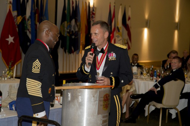 Brig. Gen. Daniel Karbler, Commander of the 94th AAMDC, and Command Sgt. Maj. Finis  Dodson, 94th AAMDC Command Sergeant Major talk about the fine ingredients added to the grog bowl during the Annual Saint Barbara's Day Ball hosted by the 94th AAMDC.