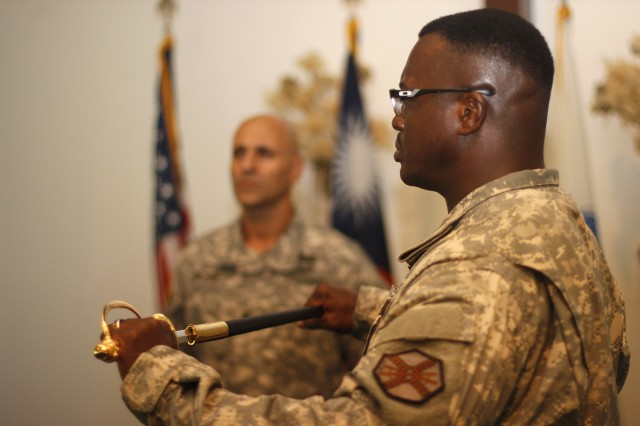 Sgt. Maj. Roderick Prioleau clasps the ceremonial sword, a symbol of adherence to military duty and honor, during his Relinquishment of Responsibility Thursday. Sgt. Maj. David Negron, looking on in the background, assisted in the ceremony.