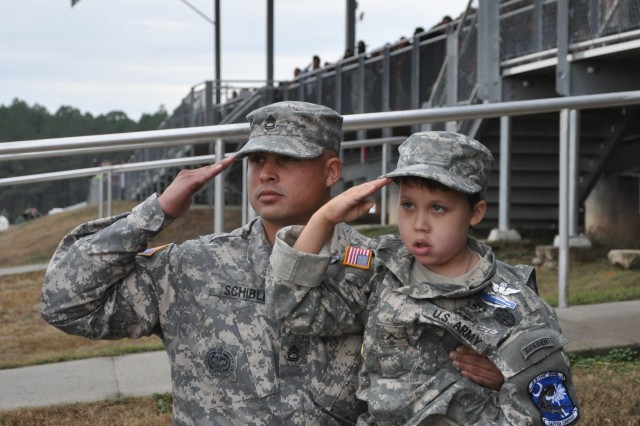 Richard Culliver, 7, and Sgt. 1st Class David Schible salute during graduation last week. Richard was granted a wish to be a Soldier for a day.