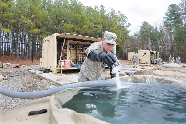 Pvt. Axel Mercado adds sodium bisulfate to a water tank during operations procedure training Dec. 6 at Tactical Water Purification System Training Site. Mercado was part of a group Romeo Company, 262nd Quartermaster Battalion, Soldiers undergoing training in the QM School's Water Treatment Specialist Course.