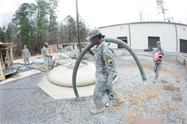 Pfc. Kimmara Casey and others move equipment during the operations phase of the Tactical Water Purification System training Dec. 6 at the TWPS Training Site. Casey is water treatment specialist course student assigned to Romeo Company, 262nd QM Battalion