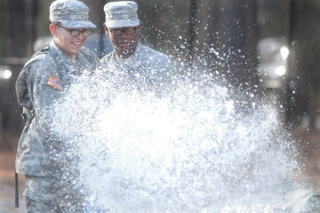 Pvt. Angel Musa and Pvt. Anthony Hart hold steady a hose as it shoots water into a tank during backwash procedure training Dec. 6 at Tactical Water Purification System Training Site. The two were part of a group Romeo Company, 262nd Quartermaster Battalion, Soldiers undergoing training in the QM School's Water Treatment Specialist Course