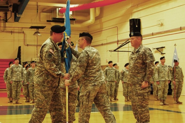 Col. Kevin Wulfhorst, commander of the 1st Military Intelligence Brigade, 100th Division (center), conducts the passing of the guidon between Lt. Col. (P) Robert Wilkinson, outgoing commander (right), and Lt. Col. Richard Chmielewski, Jr., incoming commander of the 5th Battalion-104th Regiment (Military Intelligence) (left). The battalion held its change of command ceremony Saturday in Barnes Field House.