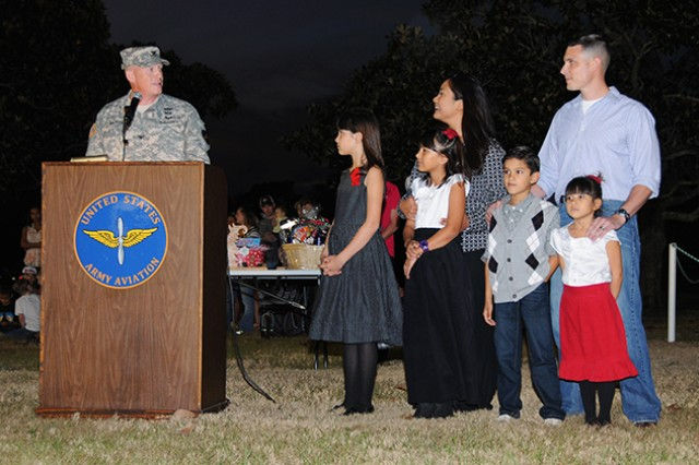 Col. Stuart J. McRae, Fort Rucker garrison commander, introduces the Eblen Family, winners of the Family of Excellence Award, during the Christmas Tree Lighting Ceremony on Howze Field Dec. 5.