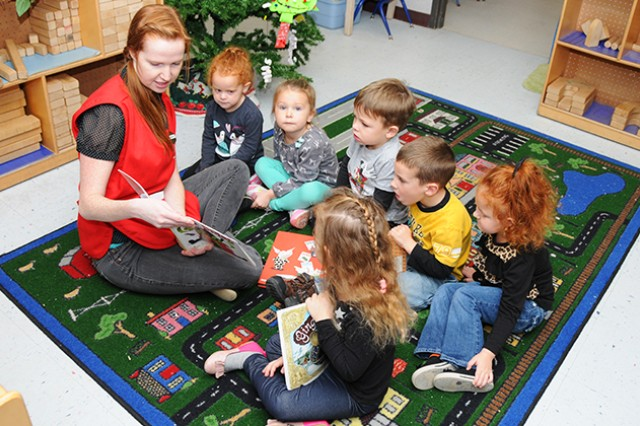 Nicole Moore, child and youth program assistant, reads a story to children at the child development center Dec. 10. The CDC and the new 24/7 Mini CDC are available for parents who need hourly childcare by appointments or on a space-available basis.