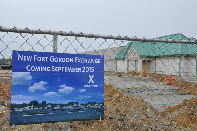 Color photos of the final view of the completed Exchange hang on the fence around the construction site of the Fort Gordon Exchange. The one-stop 80,000 additional feet of shopping space will also house the Class 6 store, the optical shop, and merchandise from the PXtra.