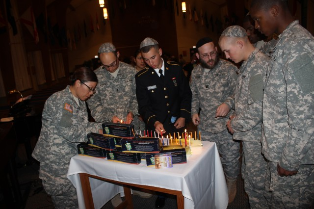 Chap. (Capt.) Mendy Stern, second from right, leads Soldiers in lighting menorahs at a Chanukah Ceremony.
