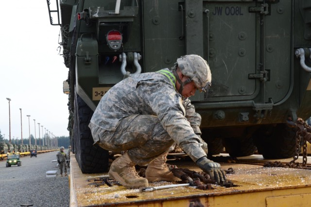 U.S. Army Pfc. William Amituanai, a Hilo, Hawaii, native and rifleman with 3-2 Stryker Brigade Combat Team, 7th Infantry Division, secures a M1126 Stryker Infantry Carrier Vehicle for rail transport Dec. 5, 2013. 3-2 SBCT Soldiers are conducting railhead operations in advance of their scheduled rotation to the National Training Center at Fort Irwin, Calif., in early January of next year. (U.S. Army photo by Staff Sgt. Chris McCullough)