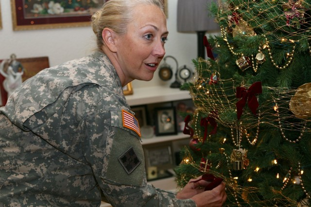 "In preparation for the 21st Annual Historical Tour of Homes, Col. Kris Kramarich, Network Enterprise Technology Command chief of staff, places a bow on the largest of the three Christmas trees on display in her home "" the Carr House. The public is invited to tour the main levels of 11 decorated homes along Grierson Avenue and Brown Parade Field, Sunday, 1 "" 5 p.m."