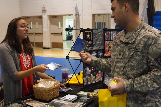"Jenna DeDominici, Army OneSource community support coordinator, hands materials to Spc. Santiago Jaramillo, Company A, 305th Military Intelligence Battalion. Army OneSource, a resource which works as a ""one-stop shop"" for all services available through the Army, participated the Resilience Rodeo at Eifler Fitness Center on Fort Huachuca, Ariz., Dec. 10, 2013."