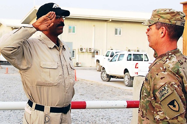 Pillai Swaminathan, who works as a security guard at AFSBn-Kandahar, greets Lt. Col. Roy Speaks, battalion commander, AFSBn-Kandahar, 401st AFSB, with a salute perfected after serving more than 26 years in the Indian Army.