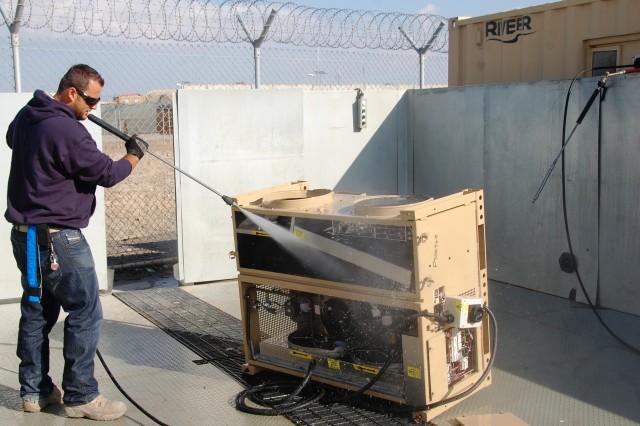 Kenana Veliu, an AFSBn-Kandahar, 401st AFSB, supply specialist from Kosovo, cleans a ECU Alaska heater in preparation for a Customs check.