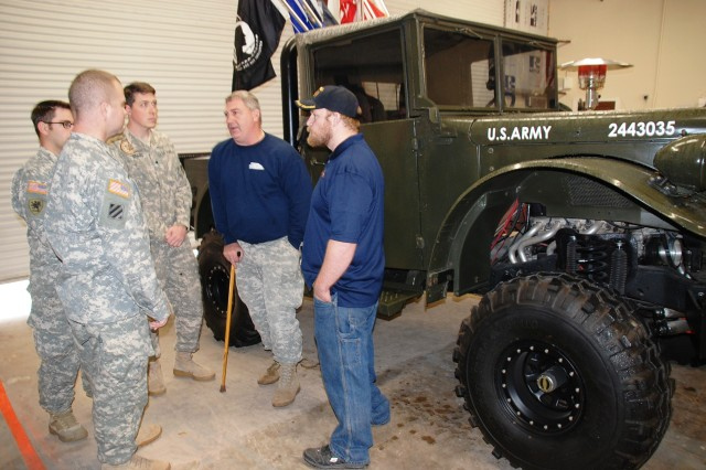 "Army veterans Chris Leverkuhn and Vic Hash talk with Soldiers from BAMC's Warrior Transition Battalion during the grand opening of the Automotivation program in Northeast San Antonio, Dec. 9, 2013. Behind them is a hybrid vehicle wounded service members put together, then dubbed ""The Beast."""