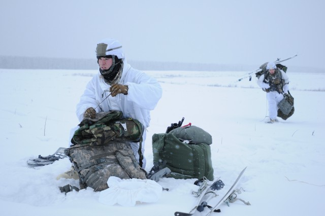 Spc. William Baker (left), an infantryman with Charlie Troop, 1st Squadron, 1-40th Cavalry Regiment, 4th Infantry Brigade Combat Team (Airborne), 25th Infantry Division, works to secure his equipment in preparation for follow-on movement after successfully exiting a C-130 Hercules Alaska Air National Guard aircraft, Dec. 12, 2013, at the Malemute Drop Zone at Joint Base Elmendorf-Richardson, Alaska. Baker and his unit exited the aircraft from the tailgate with a full arctic combat load, demonstrating their unique ability to rapidly deploy troops into arctic environments in response to a variety of contingencies.