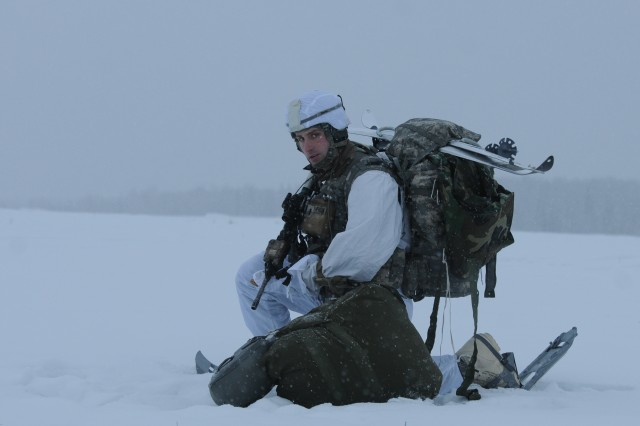 First Lt. David Pearson with the 1st Squadron, 40th Cavalry Regiment, 4th Infantry Brigade Combat Team (Airborne), 25th Infantry Division, takes a knee as he waits for another paratrooper to secure his equipment after successfully exiting a C-130 Hercules Alaska Air National Guard aircraft, Dec. 12, 2013, at the Malemute Drop Zone at Joint Base Elmendorf-Richardson, Alaska. Pearson and his unit exited the aircraft from the tailgate with a full arctic combat load, demonstrating their unique ability to rapidly deploy troops into arctic environments in response to a variety of contingencies.