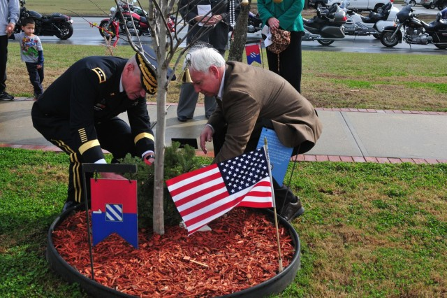 Maj. Gen. John M. Murray, 3rd Infantry Division commanding general, and retired Lt. Gen. William Webster, former 3rd Infantry Division commanding general, place a wreath at the base of Medal of Honor recipient Sgt. 1st Class Paul R. Smith's memorial tree, Dec. 14,  2013, as part of the seventh annual Wreaths for Warriors Walk event at Fort Stewart, Ga. The wreaths will remain on display at Warriors Walk throughout the holiday season.