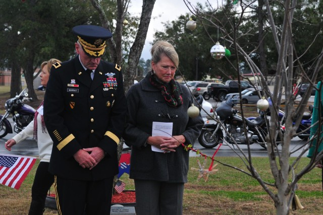 Maj. Gen. John M. Murray, 3rd Infantry Division commanding general, and his wife, Jane, take a moment to pay their respects, Dec. 14, 2013, at Sgt. 1st Class Paul R. Smith's memorial tree after placing a holiday wreath at its base at Fort Stewart, Ga. Smith, a Medal of Honor recipient, is one of 466 fallen heroes remembered at Fort Stewart's Warriors Walk with an Eastern Redbud tree.