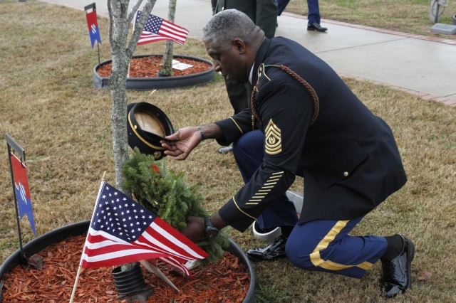 Command Sgt. Maj. Edd Watson, senior enlisted adviser for the 3rd Infantry Division, places a holiday wreath on the memorial for Sgt. 1st Class Lonnie J. Pason, a fallen Soldier with the 2nd Armored Brigade Combat Team, during a ceremony at Warriors Walk, Dec. 14, 2013, at Fort Stewart, Ga. The event is to remember the fallen Soldiers of Fort Stewart during the holiday season.