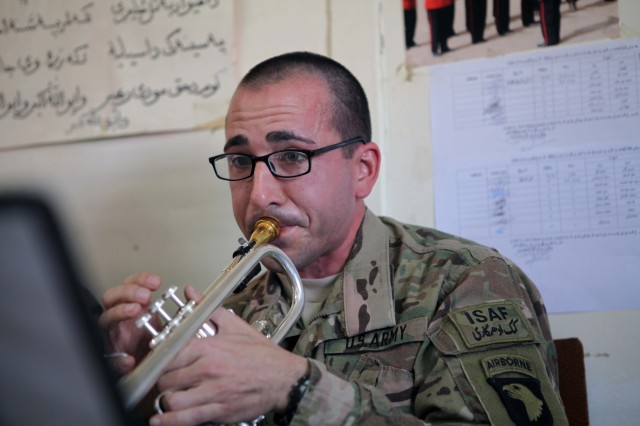 U.S. Army Sgt. Lee Lamb with Headquarters and Headquarters Battalion, 101st Airborne (Air Assault) Division Band plays his trumpet during a musical selection on Forward Operating Base Thunder, Paktiya province, Afghanistan, Dec. 14, 2013. 101st Airborne donated over forty thousand dollars worth of musical instruments and equipment to the 203rd Corps band. The new musical instruments replace the antiquated equipment the 203rd Corps used for years. (U.S. Army photo by Spc. Ryan D. Green/Released)