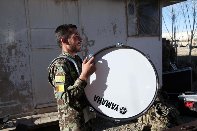 An Afghan National Army 203rd Corps band member happily walks away with a new Snare Drum set on Forward Operating Base Thunder, Paktiya province, Afghanistan, Dec. 14, 2013. 101st Airborne (Air Assault) Division donated over forty thousand dollars worth of musical instruments and equipment to the 203rd Corps band. The new musical instruments replace the antiquated equipment the 203rd Corps used for years. (U.S. Army photo by Spc. Ryan D. Green/Released)