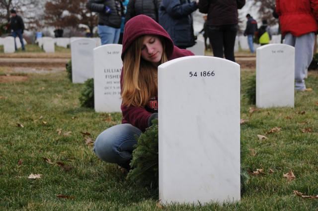 """More than 143,000 wreaths were placed on gravesites, Dec. 14, 2013, as part of the 22nd annual """"Wreaths Across America"""" event at Arlington National Cemetery in northern Virginia. For more than two decades now, volunteers have gathered to place wreaths on gravesites in the cemetery. The wreaths are manufactured by Worcester Wreath Company, of Harrington, Maine, and come to the cemetery by truck over the week in advance of the event."""