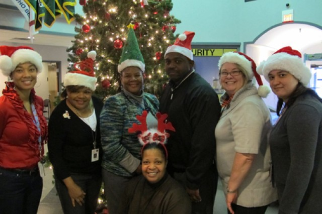 """Members of Huntsville Center's Installation Support and Programs Management Directorate's Facilities Division wear festive holiday hats during Christmas Hat Day Dec. 10 at Huntsville Center. The team is celebrating """"The 12 Days of Christmas"""" at the center Dec. 9-20 to reduce stress in the workplace this holiday season."""