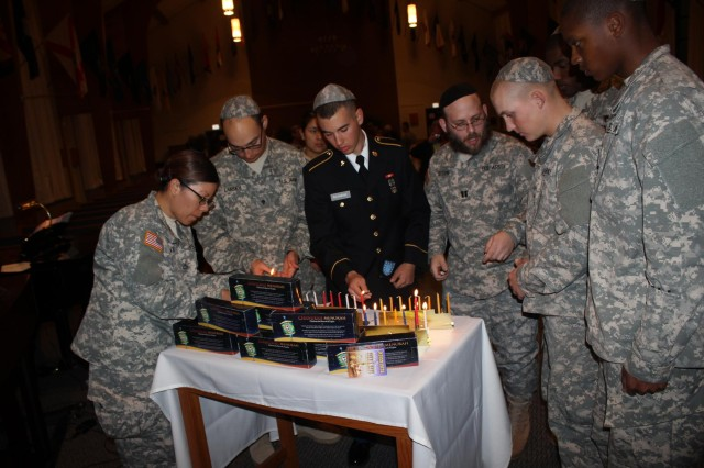 Capt. Mendy Stern, chaplain, second from right, leads soldiers in lighting menorahs at a Hanukkah Ceremony.