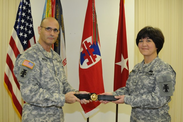 Maj. Gen. William M. Buckler, Jr., commander of 412th Theater Engineer Command, presents deputy commander Brig. Gen. Miyako N. Schanely with her General Officer Belt during her promotion ceremony held at the TEC headquarters in Vicksburg, Miss. Schanely, a resident of Black River, N.Y., is the first female Japanese-American, first female Engineer in the U.S. Army Reserve and second in the Army to be promoted to general officer.