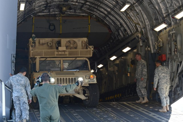 A Soldier directs the Humvee into a C-17 Globemaster III aircraft on Wheeler Army Airfield, Hawaii, Dec. 16.