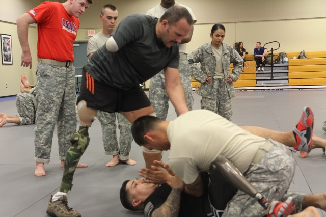 Wounded warrior Spc. Kristian Cedeno demonstrates how he is able to fight and help their fellow Soldiers during level 2 Army Combatives certification class at Fort Stewart, Ga.