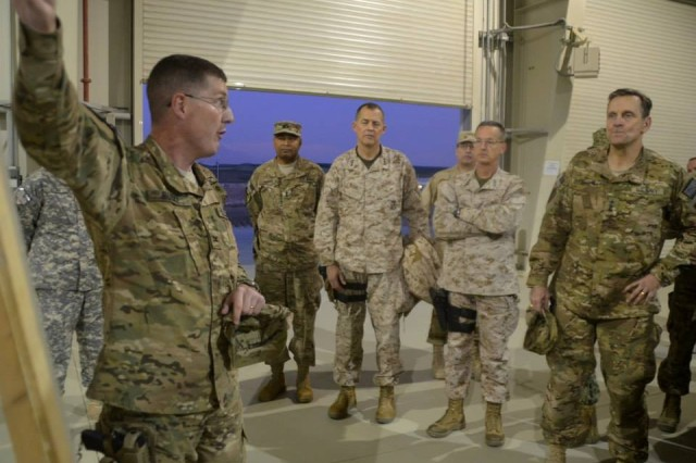 Col. Edward Burke, 401st Army Field Support Brigade commander, briefs Vice Adm. Mark D. Harnitchek, director of the Defense Logistics Agency and other DOD logistics leaders about the current retrograde process.