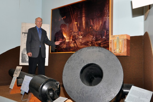 In happier times, arsenal museum Curator Robert Pfeil stands in an exhibit area three years ago.  The cannon and mortar have since been removed as part of a major reorganization being conducted by the Center of Military History.