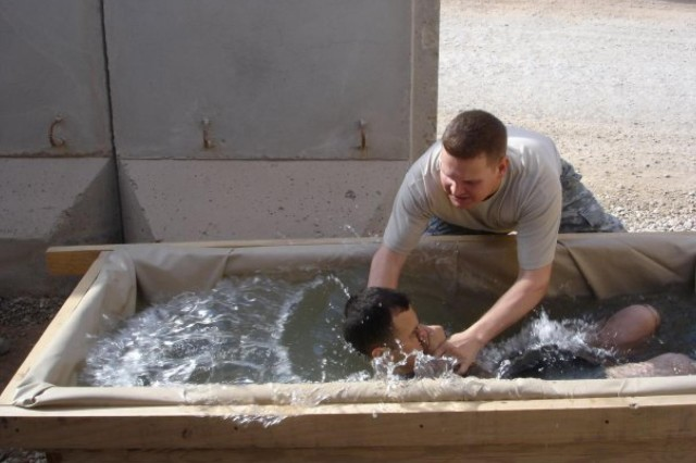 "Maj. Marshall Coen (right), a Killeen, Texas, native and chaplain for the 1st ""Ironhorse"" Brigade Combat Team, 1st Cavalry Division, baptizes a Soldier during his deployment with the 1st Battalion, 504th Parachute Infantry Regiment, 82nd Airborne Division, Jan. 24, 2010, at Al Asad Air Base, Iraq. Coen recalled the baptism as one of many rewarding moments of his career, but said his most rewarding moment was coming home from deployment and seeing his wife and family. The father of three boys, Coen said his greatest accomplishment is his family. (Photo courtesy of Maj. Marshall Coen, 1st BCT, 1st Cav. Div.)"