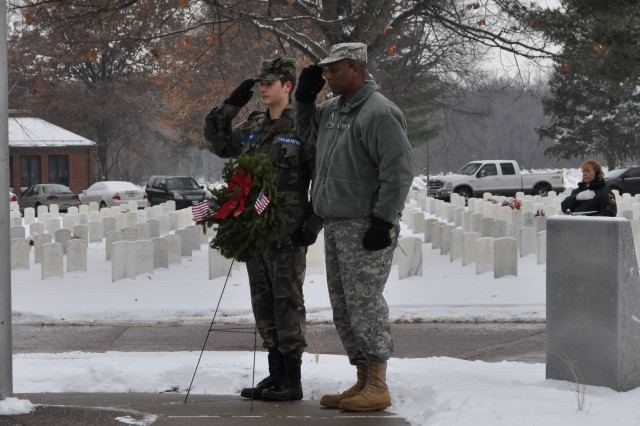 JMC Command Sgt. Maj. Anthony Bryant gives a hand salute with a Civil Air Patrol cadet, Dec. 15, 2013, during a Wreaths Across America ceremony at the U.S. Army Garrison-Rock Island Arsenal National Cemetery.