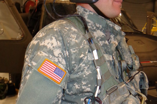 An ARNG helicopter pilot wears a helmet-mounted accelerometer and data collection unit.