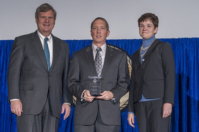 Agriculture Secretary Tom Vilsack and Agriculture Deputy Secretary Krysta Harden present the Secretary's Honor Award to Edgewood Chemical Biological Center, Agent Chemistry Team U.S. Army, at Aberdeen Proving Ground, in Maryland Group leader Frederic Berg for partnering with the U.S. Department of Agriculture (USDA) to conduct critical chemical threat agent research to ensure that the Nation's food supply is safe and reliable at the 2013 Secretary's Honor Awards in the Jefferson Auditorium at USDA in Washington, D.C. on Wednesday, Dec. 11, 2013. USDA photo by Lance Cheung.