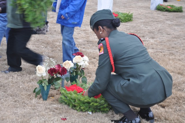 A JROTC cadet from Westwood High School in Blythewood straightens a ribbon on a wreath after placing it on a grave.