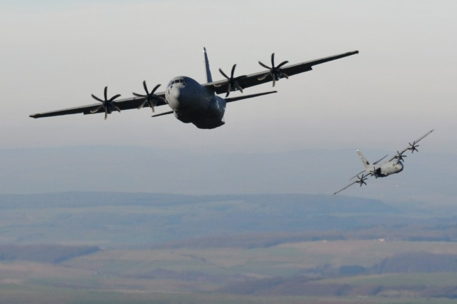 Two C-130 aircraft line-up in preparation to drop U.S. and partner nation paratroopers during an airborne operation over Drop Zone Alzey, near Kaiserslautern, Germany,  Dec. 17, 2013.  The operation, which was coordinated by the 21st Theater Sustainment Command's 5th Quartermaster Detachment (Airborne), was conducted as a part of International Jump Week in which paratroopers from the U.S., Germany, France, Spain, the Netherlands and Estonia perform airborne operations together in an effort to build on relationships and interoperability.