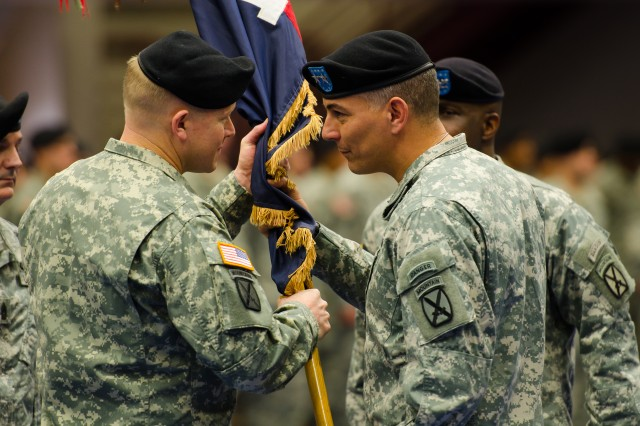 "Col. Frederick ""Mark"" O'Donnell accepts the 1st Brigade Combat Team guidon from Maj. Gen. Steven J. Townsend, Fort Drum and 10th Mountain Division (LI) commander, during a change of command ceremony Friday at Magrath Sports Complex, as outgoing commander Col. Stephen L.A. Michael looks on."